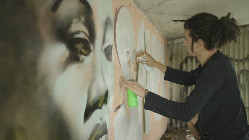 4K Talented young graffiti street artist working on a mural in urban area Dec 2016-UK