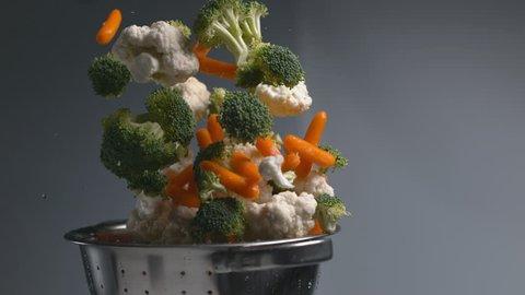 Vegetables flying out of colander in super slow motion, shot on Phantom Flex 4K