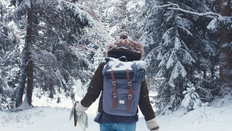 FOLLOW Young female hiking with a backpack in beautiful winter forest, holding paper map in hands. 4K UHD, 60 FPS SLO MO, RAW edited footage