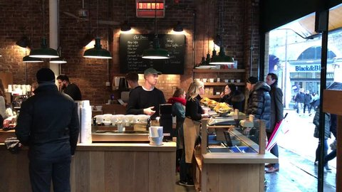 LONDON - JANUARY 12, 2017: Baristas and employees serve customers beans by weight and hot caffeinated beverages at Monmouth Coffee shop at Borough Market in London Bridge, Southwark, London, UK.