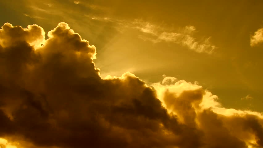 Beautiful cloudscape with large, building clouds and sunset behind shining sun