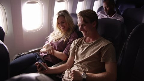 Couple looking at mobile phone together on airplane flight