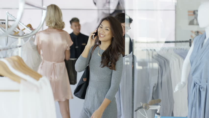 4K Beautiful woman talking on phone while she shops in boutique clothing store. Dec 2016-UK | Shutterstock HD Video #23051692