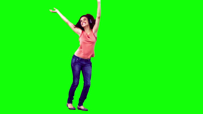 Happy woman in slow motion dancing against a green background #2310083