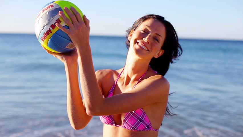 Smiling brunette playing volleyball on the beach