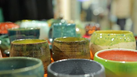 Lady choosing decorative handmade pottery bowls at ceramic store, shopping. Woman holding local souvenirs, searching for present, exhibition sale, art. Female shopaholic buying traditional plates