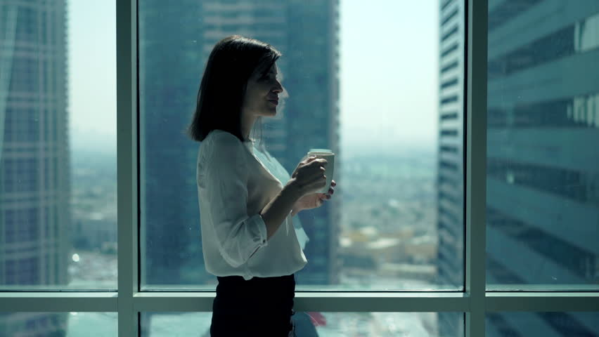 Young businesswoman relaxing and drinking coffee standing by window in office   | Shutterstock HD Video #23137273