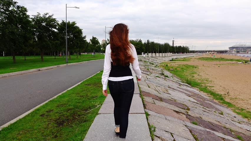 Gorgeous young formal dressed woman in white shirt ramble along park promenade, at waterfront of Finland Gulf. Sandy beach on right side, slow motion follow camera. Long brown tresses fly in air