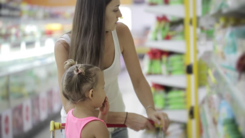 Young attractive woman with cute daughter in shopping cart choosing a vegetable oil in grocery section at supermarket | Shutterstock HD Video #23156353
