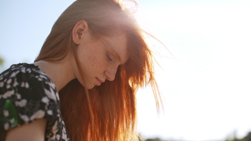 Dreamy redhead girl sitting watching touching hair while wind genlty blowing in slowmotion. Close up