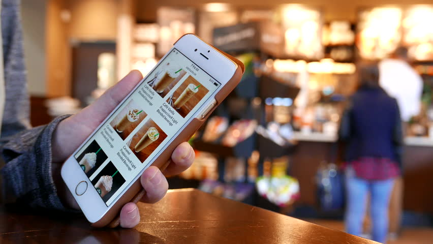 Port Moody, BC, Canada - September 12, 2016 : Motion of woman browsing Starbucks drink menu on phone inside Starbucks store with 4k resolution.