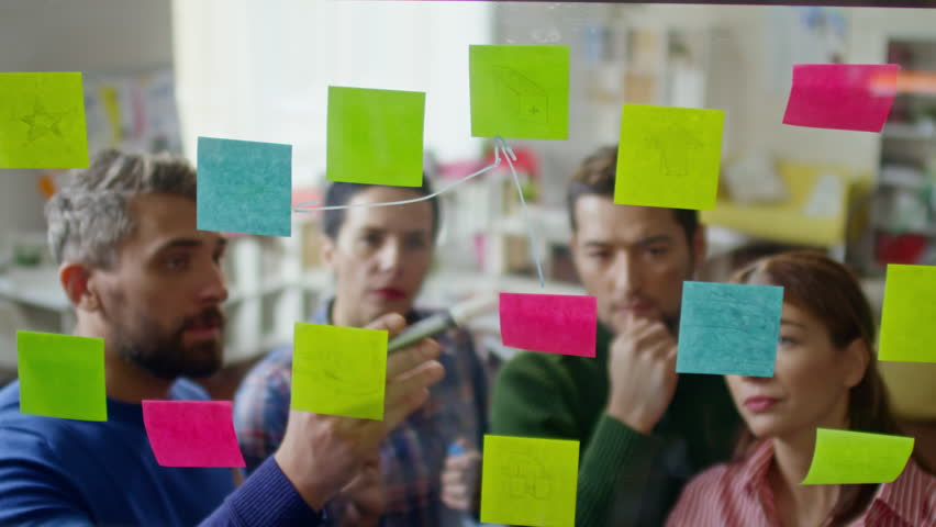 High angle shot of startup workers looking at glass wall planner with post-it notes and linking ideas on them by drawing arrows