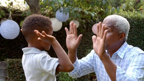Young black boy playing clapping game with grandad in garden
