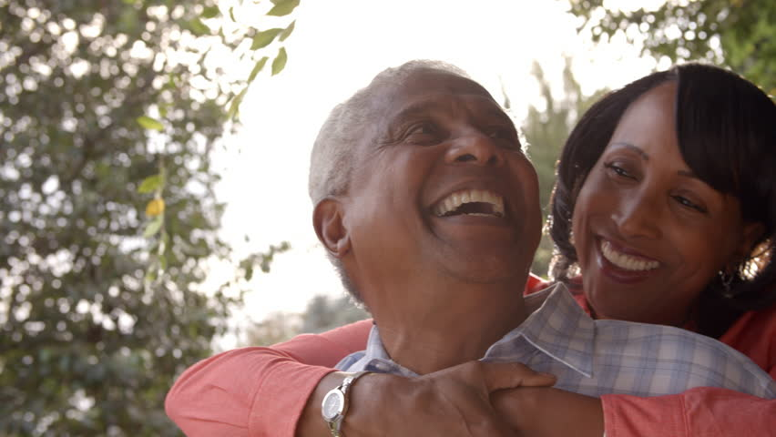 Senior black couple piggyback in garden, close up