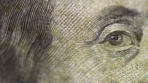 Tracking macro of Benjamine Franklin's face on the US one hundreed dollar bill. US dollars background.