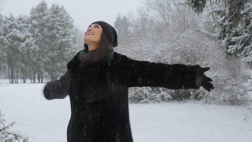 Beautiful woman is dancing in a winter park. It is snowing. She is happy in winter. Smiling. Slow motion. Winter park. Winter forest.