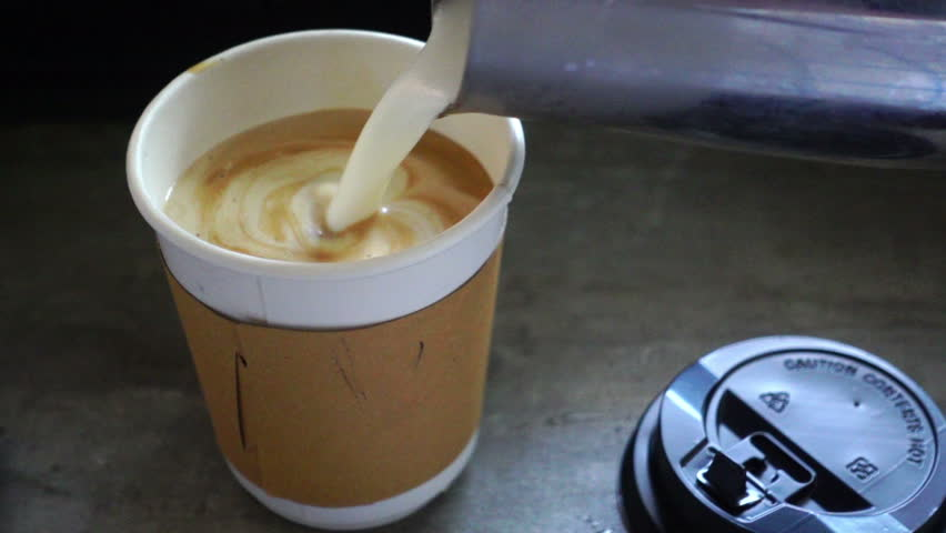 Pouring stream milk into a cup of take away coffee, slow motion  #23217463