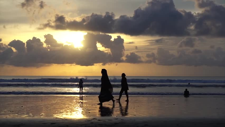 A Muslim woman is photographed walking on the beach at the sunset time | Shutterstock HD Video #23231983