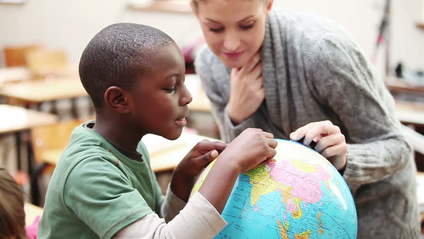 Pupil and teacher looking at a globe in the classroom