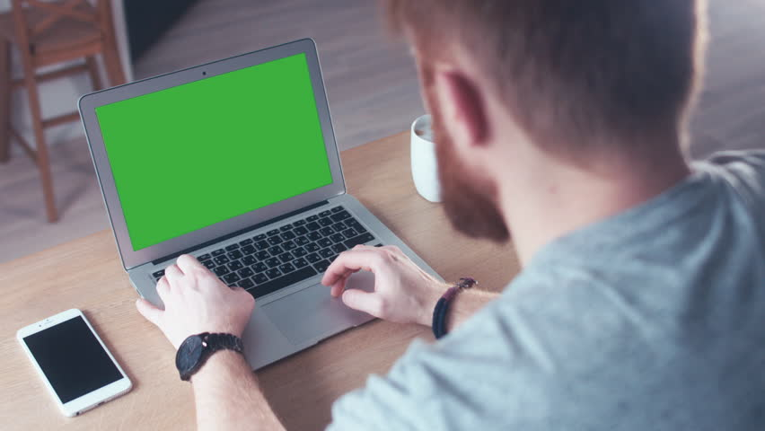 Over the shoulder shot of a young Caucasian man working from home on a laptop, green screen chroma key. 4K UHD 60 FPS slow motion | Shutterstock HD Video #23252695
