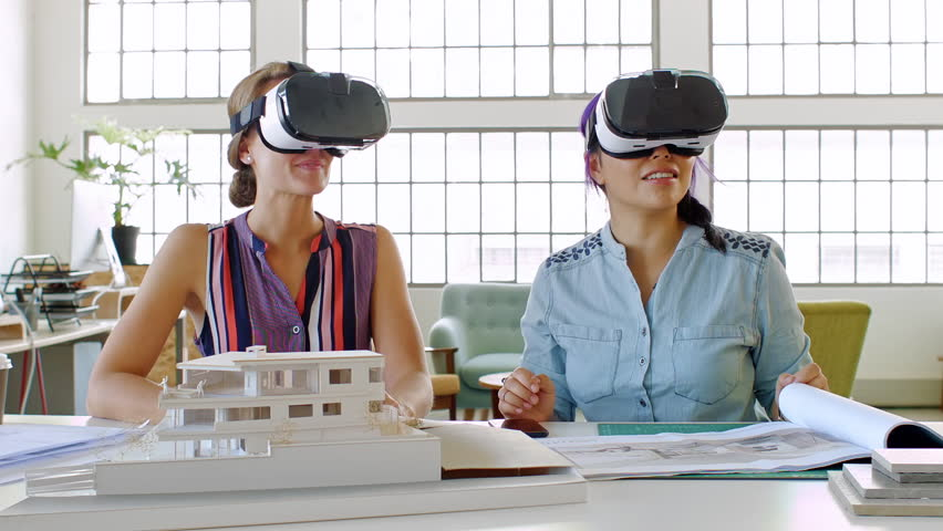 Female architects exploring virtual reality projects, future of architecture and building industry