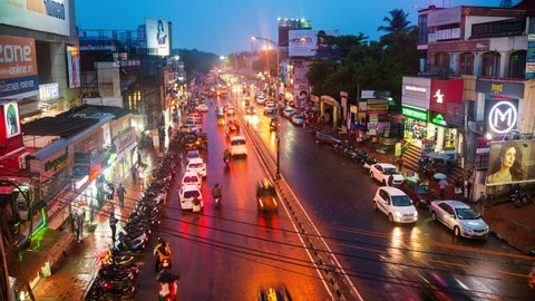 TRIVANDRUM, INDIA - MAY 15, 2016: Night traffic lights in the center of the capital of Kerala - Trivandrum, India. Various shops, cafes and restaurants. Illumination. Time-lapse at sunset