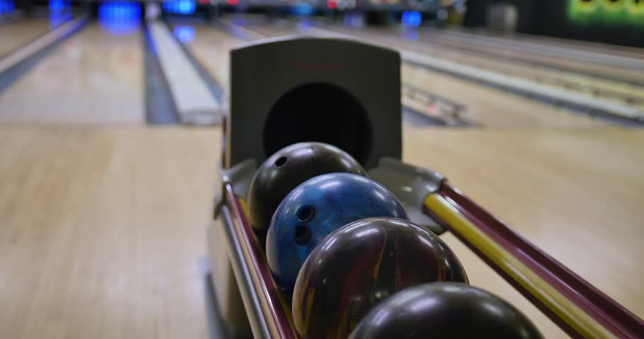 Slow tracking shot of people getting their balls from the ball return tray of a bowling alley. Extreme shallow DOF.