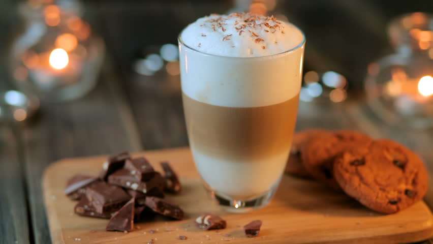 Beautiful composition - hot coffe latte cappucino with oatmeal cookies and chocolate pieces in a transparent glass. The glass stands on a wooden stand. Behind the candles are burning