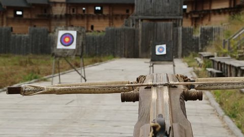 Crossbow is aimed at a target. Old wooden arbalest and targets at background. Ancient ballista