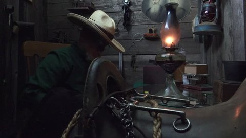 Western cowboy with hat in the old West rustic cabin or bunkhouse using a kerosene lantern loads the ammo into a double barreled shotgun.