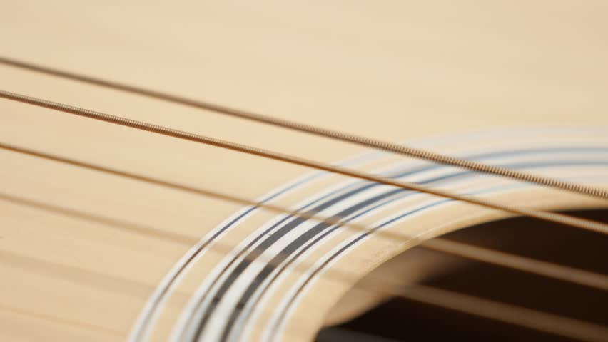 Plucked wooden acoustic guitar string shallow DOF 4K 2160p 30fps UltraHD panning footage - Detailed  instrument body slow pan 3840X2160 UHD video