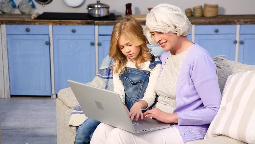Granny and her little girl using laptop computer at home. Pretty granddaughter helping her granny to log in while sitting on sofa or couch at home. | Shutterstock HD Video #23330473