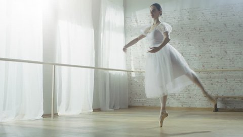 Young and Beautiful Ballerina Dances Energetically but Gracefully on Her Pointe Ballet Shoes, She's Spinning. She's Wearing White Tutu Dress. Shot on RED EPIC-W 8K Helium Cinema Camera.