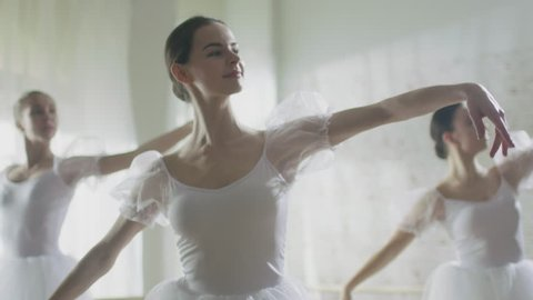 Mid Shot of Three Beautiful and Young Ballerinas Wearing White Tutus and Dancing. Shot Taking Place on a Sunny Morning in a Bright Studio. In Slow Motion.  Shot on RED EPIC-W 8K Helium Cinema Camera.