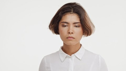 Sad thoughtful young beautiful brunette east asian female in shirt standing in hesitation on white background