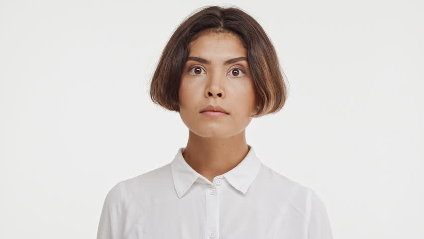 Young beautiful brunette east asian female in shirt screaming wow in surprise on white background