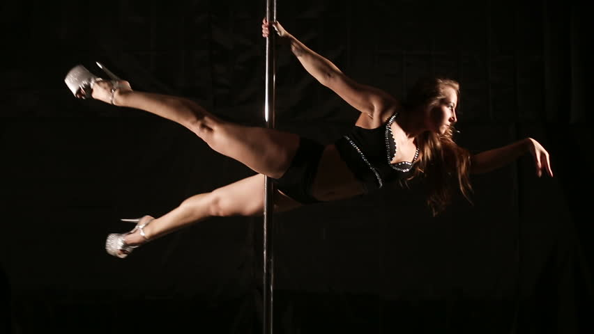 Beautiful slim girl with pylon. Female pole dancer woman dancing on a pole on a black background. Strong and graceful girl dancing on pylon. Girl easily performs complex dance steps on pylon | Shutterstock HD Video #23352193