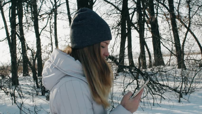 A Portrait girl walks and Using smartphone on the phone through the woods in winter in slow motion | Shutterstock HD Video #23352313