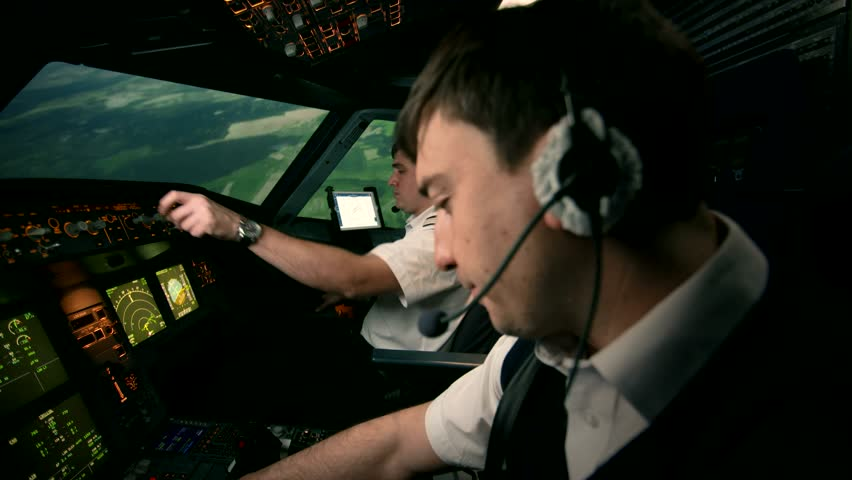 Side view of modern passenger airplane cabin. Two professional pilots in the cockpit or flight deck of a perform turn to set the course of flight. At the background of green