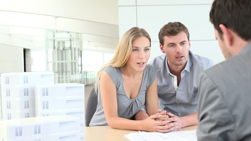 Couple in real-estate agency talking to salesman