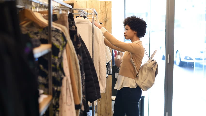 535a113dfe Young woman in boutique selecting new clothes to buy. Happy smiling girl  with curly hair looking at red dress in a fashion store.