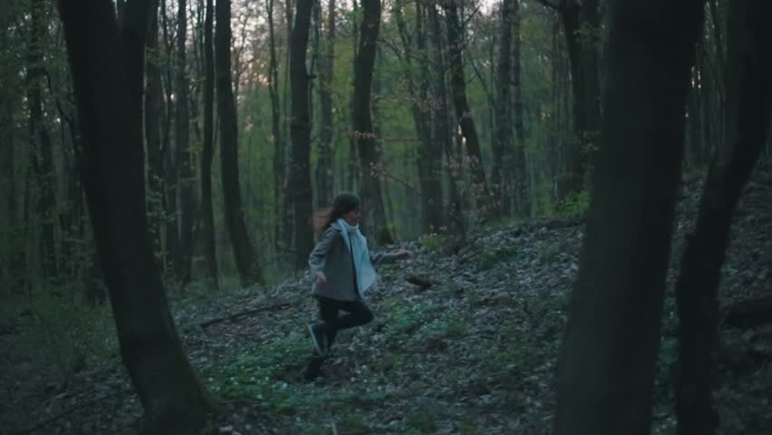 Little European girl with a long hair, brown jacket, black pants, sneakers and bright blue scarf. A scared little child is running through the dark deserted forest. Nightmare, loneliness.