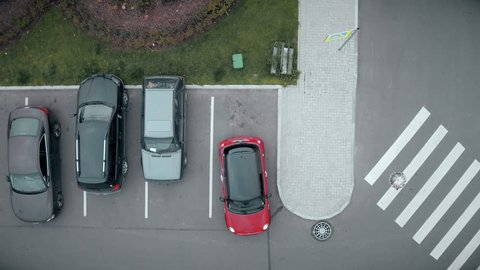 Saint-Petersburg, Russia - october 20, 2016 Upcoming passenger car occupy only free parking place at outdoor parking slot near shopping or business center in the early morning. Top aerial shot