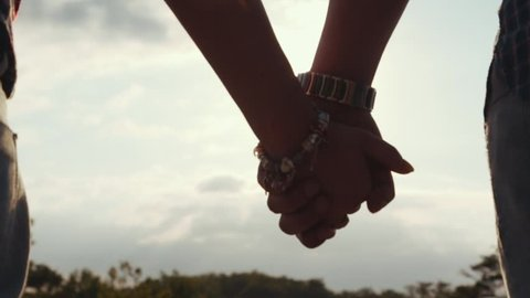 Few shots of adorable couple in casual clothes holding their hands on the high rocky mountain hill surrounded by green forest in a bright sunlight. Forever in love. Romantic atmosphere.