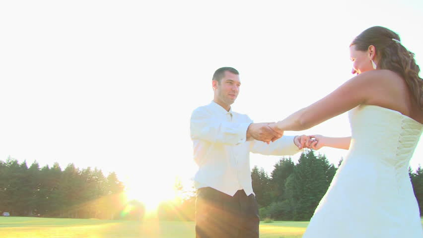 Bride and groom spinning, kissing and smiling on their wedding day.