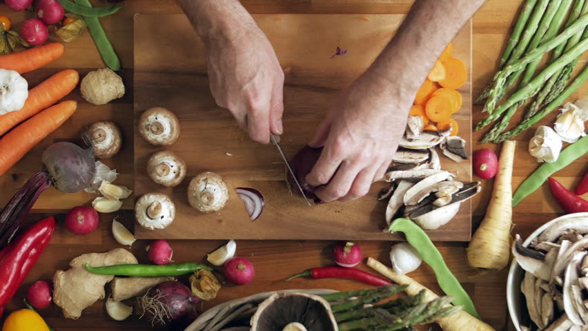 Directly above shot of man cutting onion on chopping board. Lockdown overhead shot of fresh vegetables on kitchen counter. Male is preparing food in kitchen at home. | Shutterstock HD Video #23396707