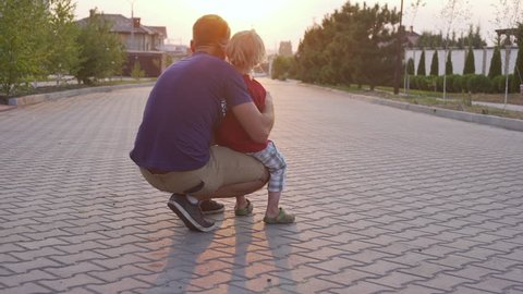 Young kid playing and his father playing with radio controlled car outside while sun setting down in slowmotion