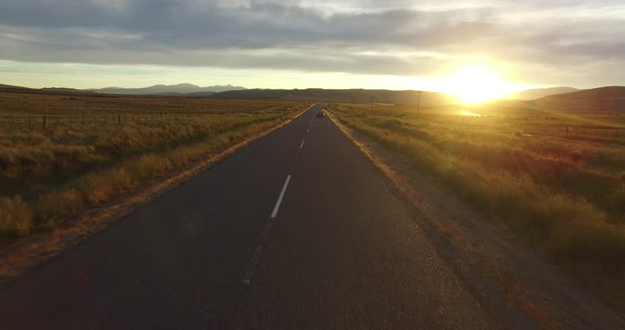Aerial drone scene of route in steppe landscape at sunset golden hour. Camera moving forward following a tracked van on the road. | Shutterstock HD Video #23399923