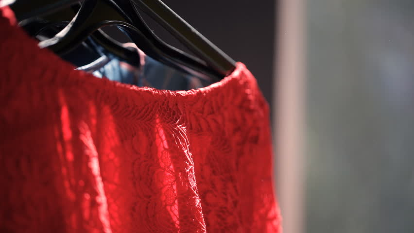 Stand with hangers with clothes. inside look at woman choice. In front of us we see rack with black plastic shoulders with red lace dress on one, behind it blue and pink cloth. Then somebody hand with