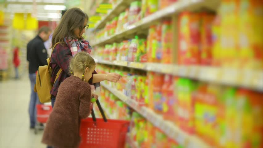 Young Mother and Little Daughter Shopping in Supermarket. Mom and Kid Puting Products on the Red Basket in the Store Together. | Shutterstock HD Video #23415847